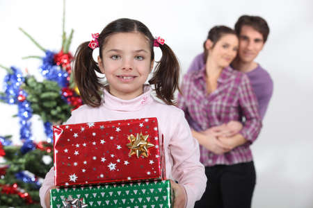 facing to camera: Girl and parents with Christmas presents