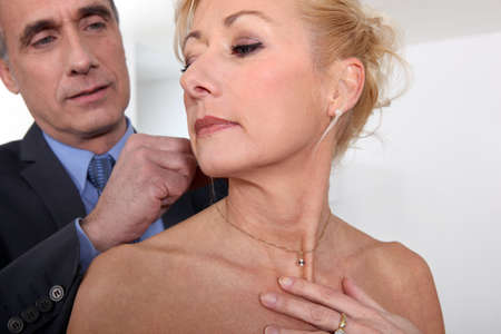 attaching: Man attaching necklace to wife Stock Photo