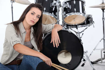 straight faced: Woman posing with her drum set