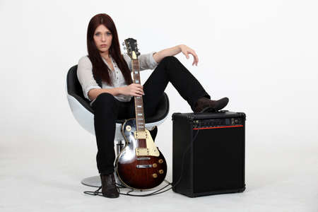 Female guitarist sitting with an amp photo