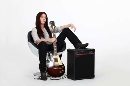 between: Woman with her foot propped on an amplifier and holding a guitar
