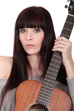 poker faced: Busker posing with her guitar Stock Photo