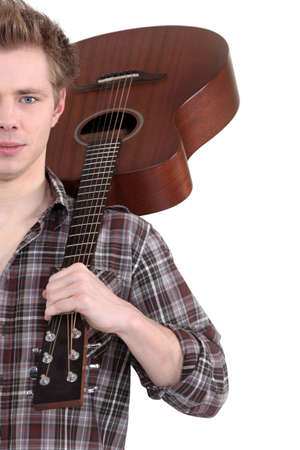 a guitarist boy playing guitar: young man with an acoustic guitar
