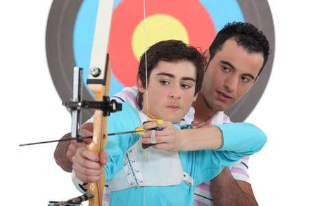 bull     s eye: Boy having archery lesson