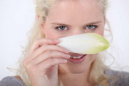 fair skinned: Woman hiding behind an endive leaf Stock Photo