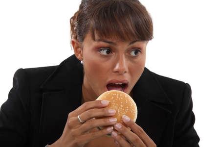 business dinner: Businesswoman biting a burger