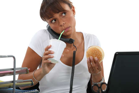 adult sandwich: young woman eating hamburger and drinking out of a straw while making a call