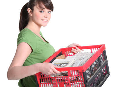 paper shredder: Woman carrying crate of newspapers to be recycled