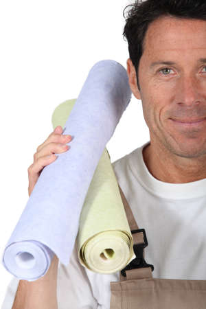 Man carrying rolls of wallpaper photo