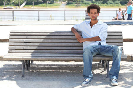 sitting on a bench: Young man sitting on a public bench