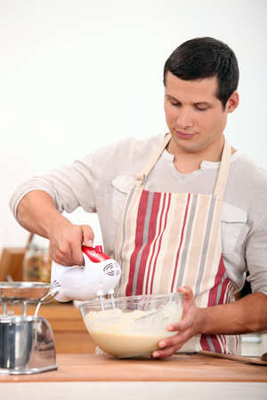 whisk: Man using electric whisk Stock Photo