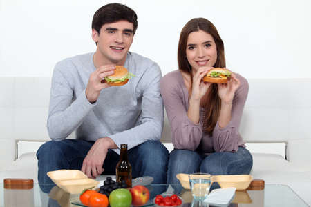 eating right: Young couple eating hamburgers