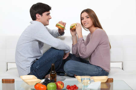 unhealthy living: couple eating hamburgers on the couch Stock Photo