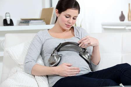 casting: Schwangere Frau, die Kopfh�rer auf ihren Bauch