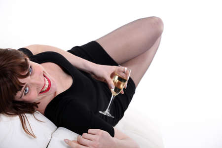 Woman lying down with glass of champagne photo