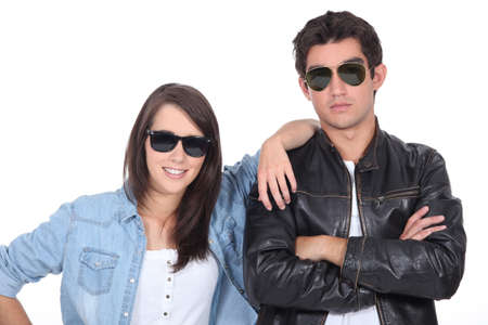nonchalant: Young couple posing in sunglasses and leather jacket