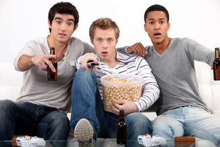 roommates: Men watching a horror movie Stock Photo