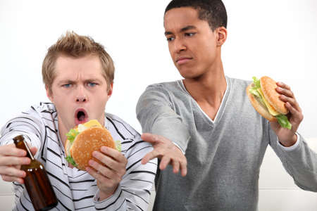 animosity: Friends eating hamburgers and watching a football game