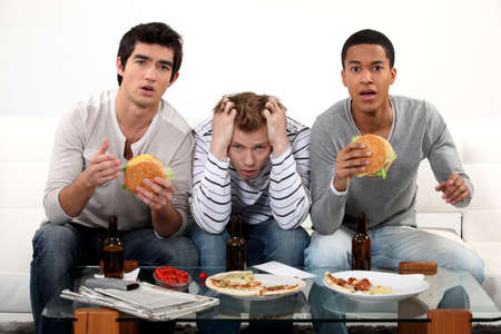 chilling: Three male friends eating burgers and watching television