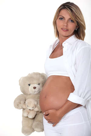 pregnant blonde: Pregnant woman with teddy bear