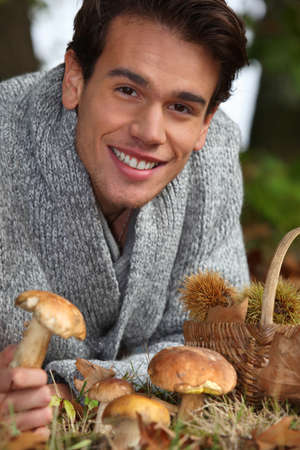 Man picking mushrooms and chestnuts in the forest Stock Photo - 15818290