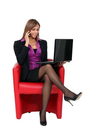 Businesswoman sitting in chair with laptop photo