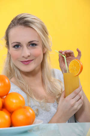 slurp: Woman with glass of orange juice Stock Photo