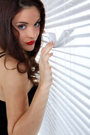 Woman spying through venetian blinds photo