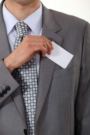 hand in pocket: A cropped picture of a businessman putting his card in his pocket
