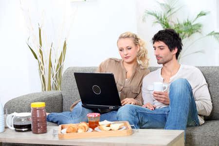 Couple eating breakfast on sofa photo