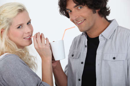 caf: couple drinking together off same mug with straw