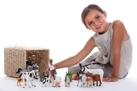 Little girl playing with toy animals photo
