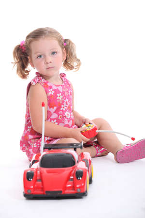 poker faced: Young girl playing with a remote-control car