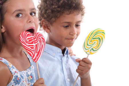 Closeup of two children eating lollipops photo