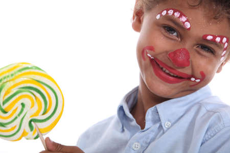 painting face: Boy made-up in clown with lollipop Stock Photo