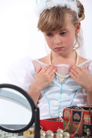 costume jewelry: Girl dressed as a princess trying on necklace