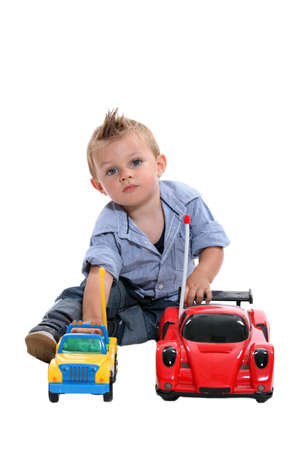 12 18 months: Tot with gelled hair playing with toy cars Stock Photo