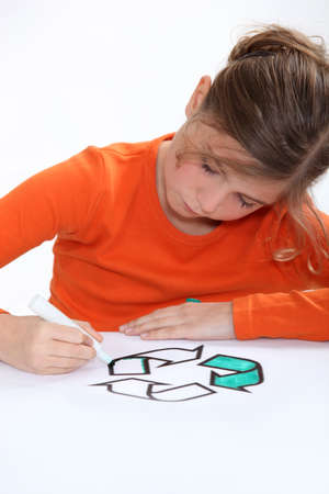 8 10 years: Girl colouring recycling sign Stock Photo