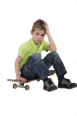discouraged: Little boy with skate board Stock Photo