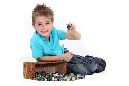 spiky hair: Little boy playing with marbles