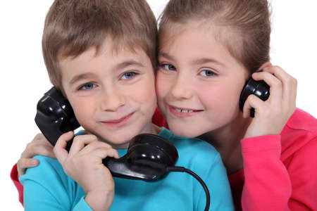 Brother and sister with old fashioned telephone photo
