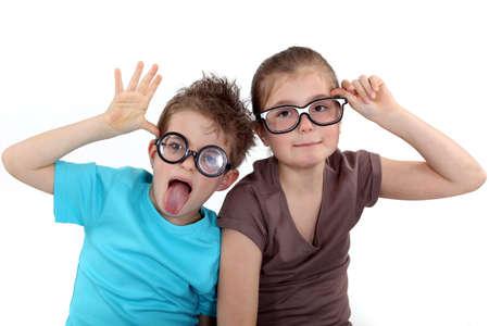 sacar la lengua: Los niños con gafas cobarde
