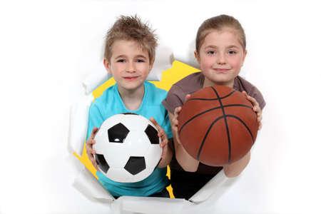 sport wear: Los ni�os con un bal�n de f�tbol y baloncesto