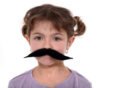 fake smile: Little girl wearing a false mustache