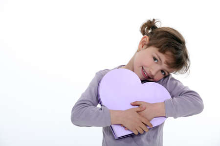one of a kind: little girl holding gift bow shaped as a heart Stock Photo