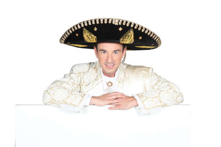 Man dressed as a mariachi with a board left blank for your message photo