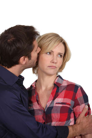 disharmony: Man whispering in an unhappy woman Stock Photo