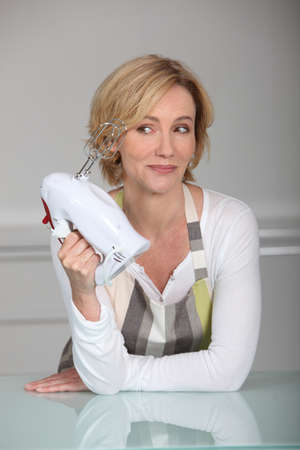 learnt: Blond woman holding electric whisk Stock Photo