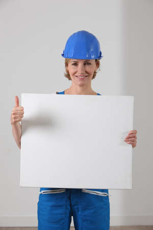 Woman in a hard hat with a blank board and the thumbs up photo