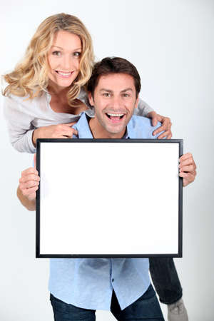 Man and woman holding up a blank poster Stock Photo - 15807449